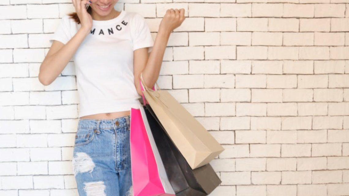 Vrouw met iPhone is een luxe kledingshopper
